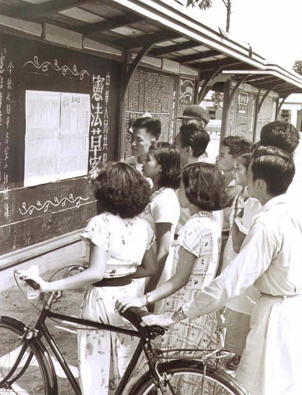 1954年,广州市华侨招待所的青年归侨阅读《宪法草案》