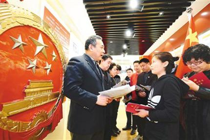 维护宪法 捍卫宪法尊严北京市卢沟桥乡司法所所长王进忠(左一)在北京第一个农村党支部大瓦窑村党史馆向群众介绍宪法修正案的主要内容。