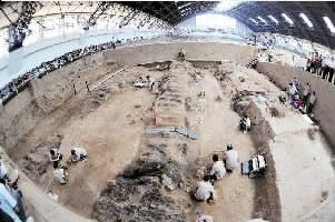 图为考古工作者在一号坑内进行工作,四周游人环顾.-文物保护法 图片